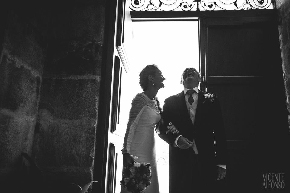 Novia y padrino riendo en la puerta de la iglesia