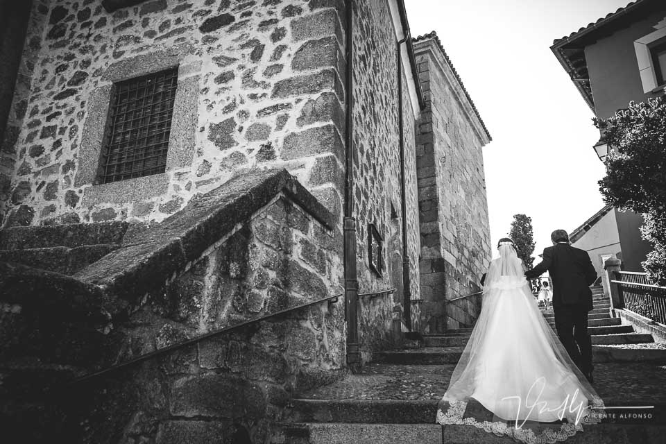 Novia subiendo escaleras de la iglesia con el padrino