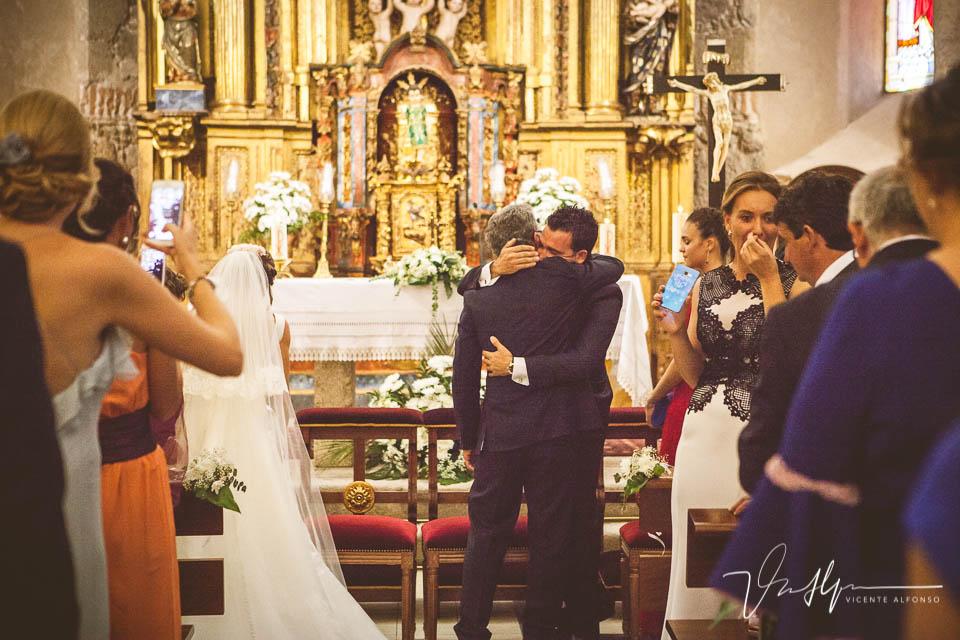 Abrazo novio y padrino en la iglesia