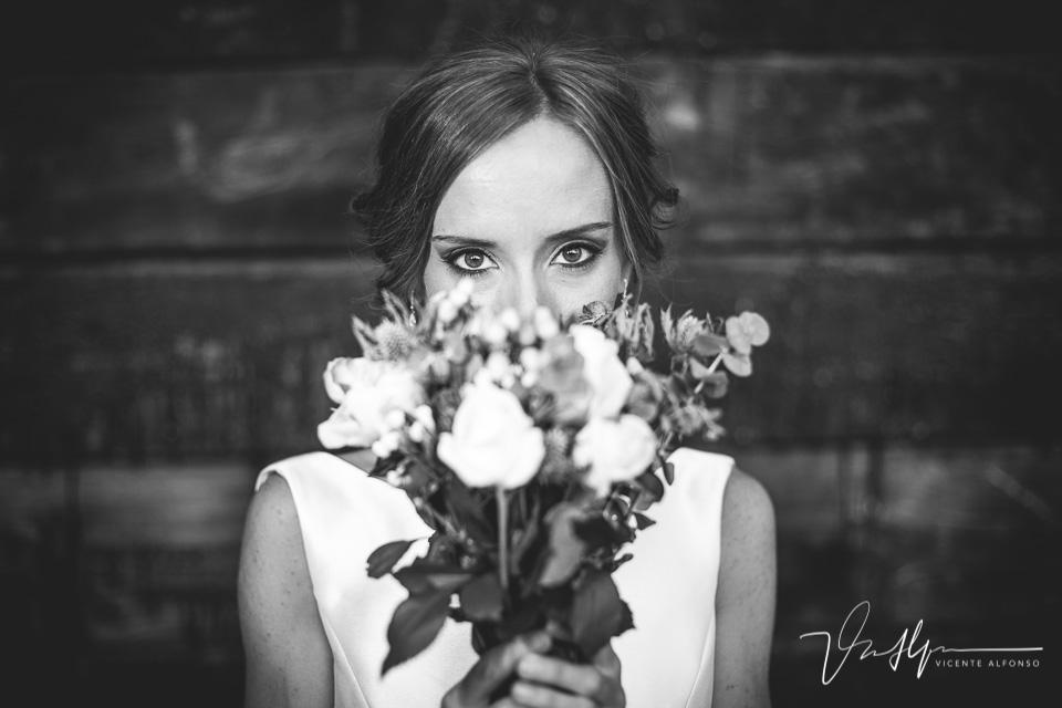 Retrato novia mirando a cámara entre el ramo de flores