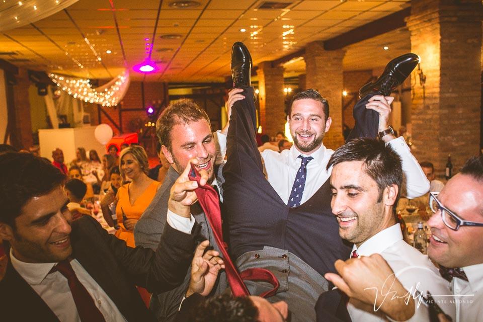 Amigos del novio cortando corbata