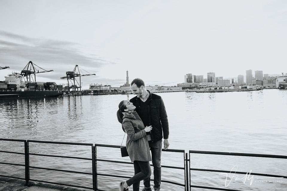 Pareja abrazada y riendo en el puerto de Génova con el faro al fondo