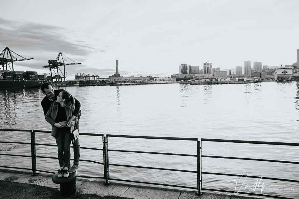Pareja abrazada en el puerto junto al faro de Génova