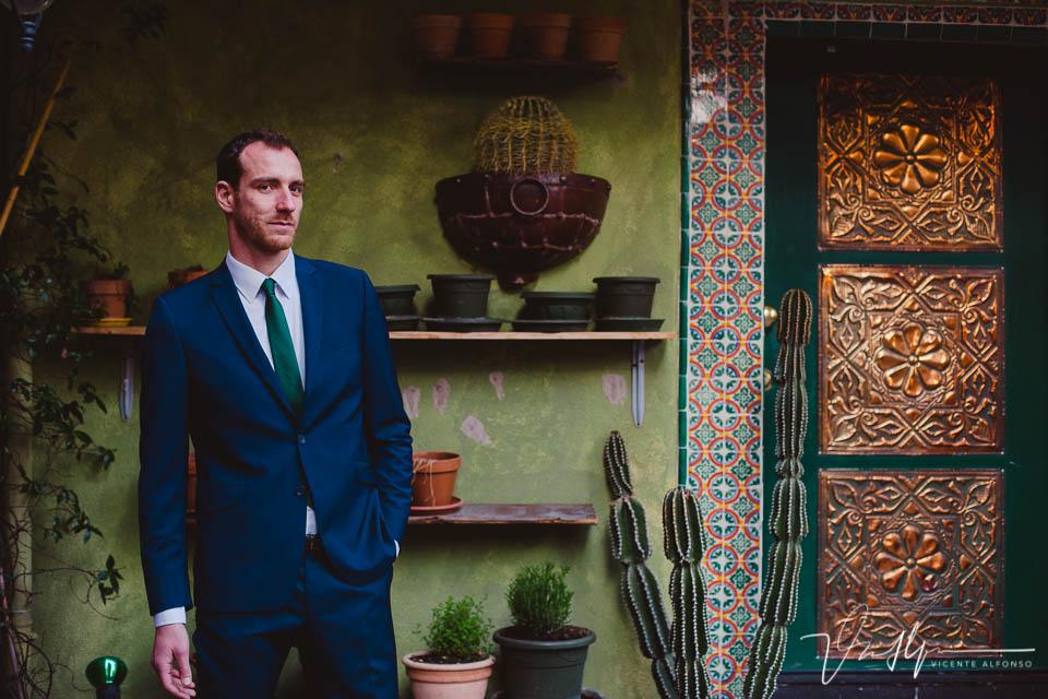 Hombre elegante y trajeado mirando a cámara junto a restaurante Mexicano