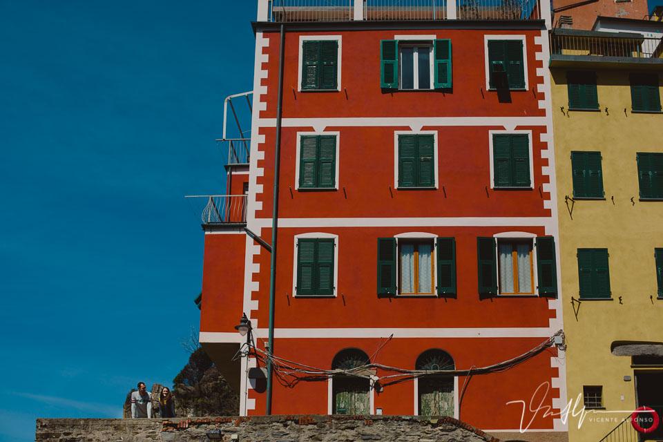 Pareja junto a edificio de colores en Cinque Terre