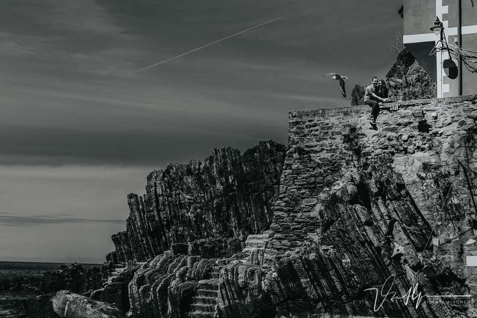 Gaviota volando en Cinque Terre con una pareja posando