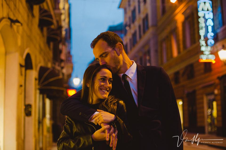 Novio besando novia en la calle principal por la noche en Genoa