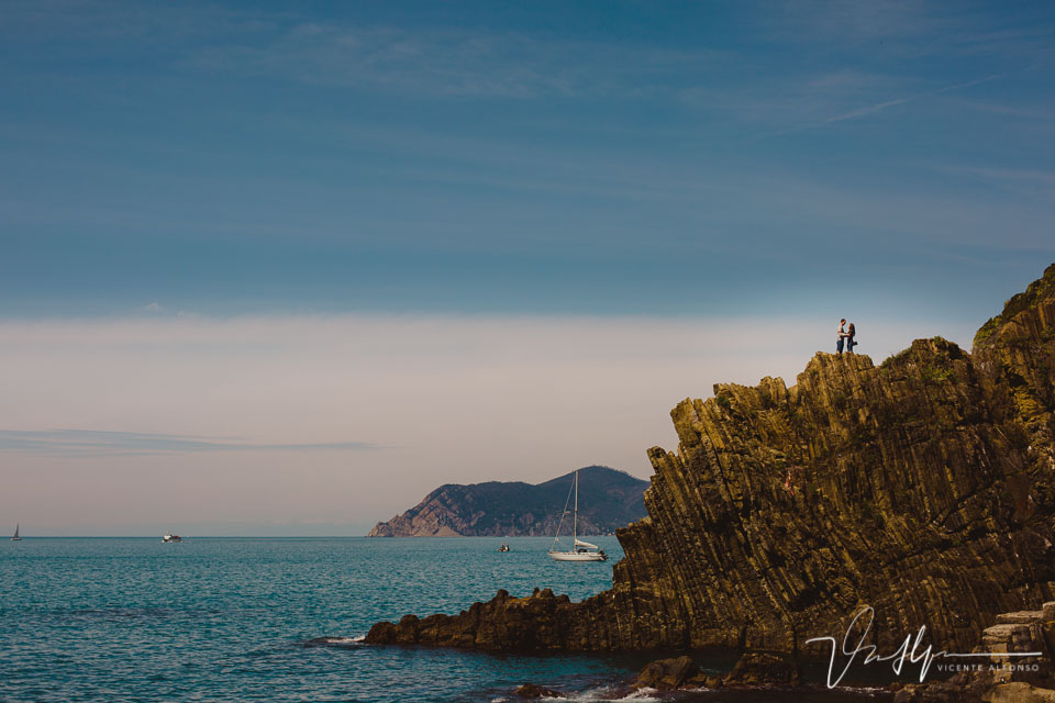 Reportaje de preboda con pareja abrazándose en un acantilado en Cinque Terre Italia