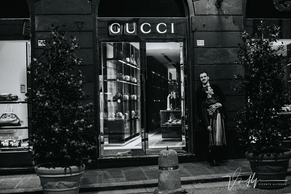 Pareja abrazándose junto a la tienda Gucci en Italia
