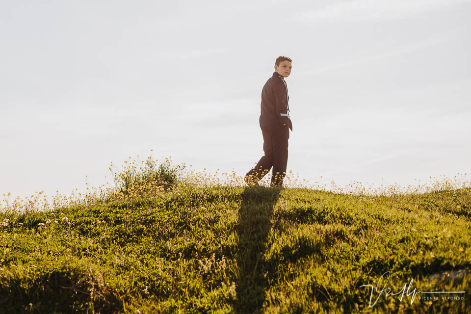 Niño de comunión de espaldas andando por el campo