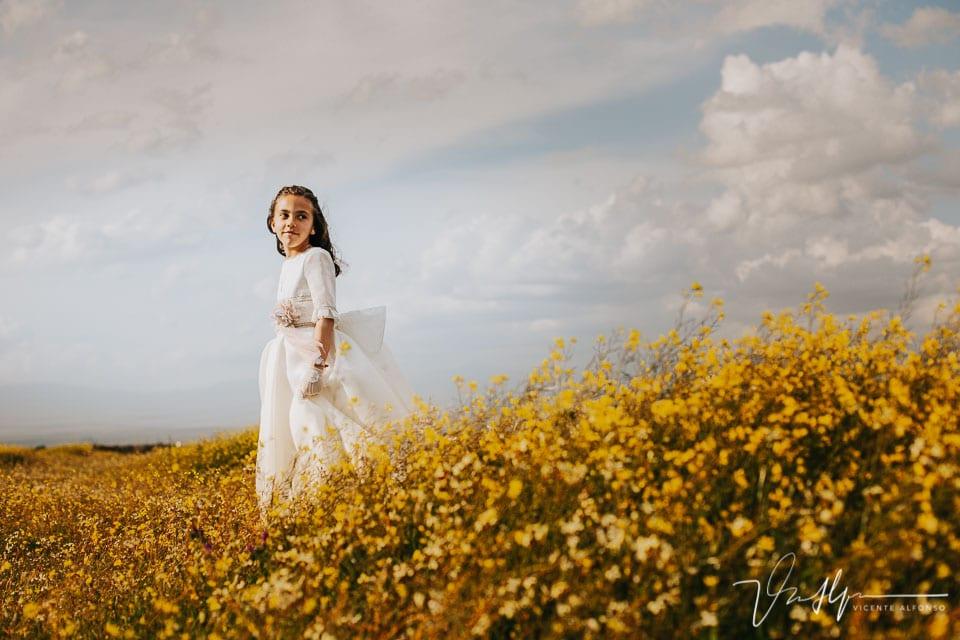 Plano general de un campo de margaritas y una niña de comunión