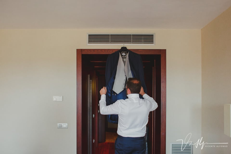 Novio cogiendo traje colgado puerta