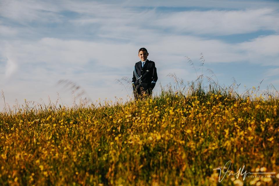 Niño de comunión de medio cuerpo entre flores y hierba