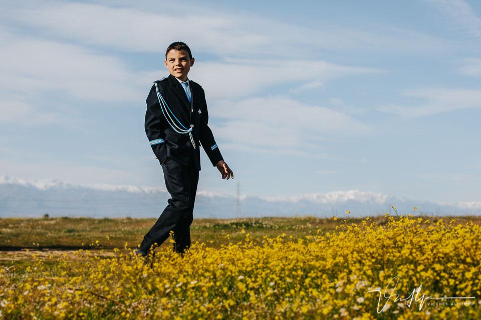 Niño de comunión sonriendo mientras anda por el campo