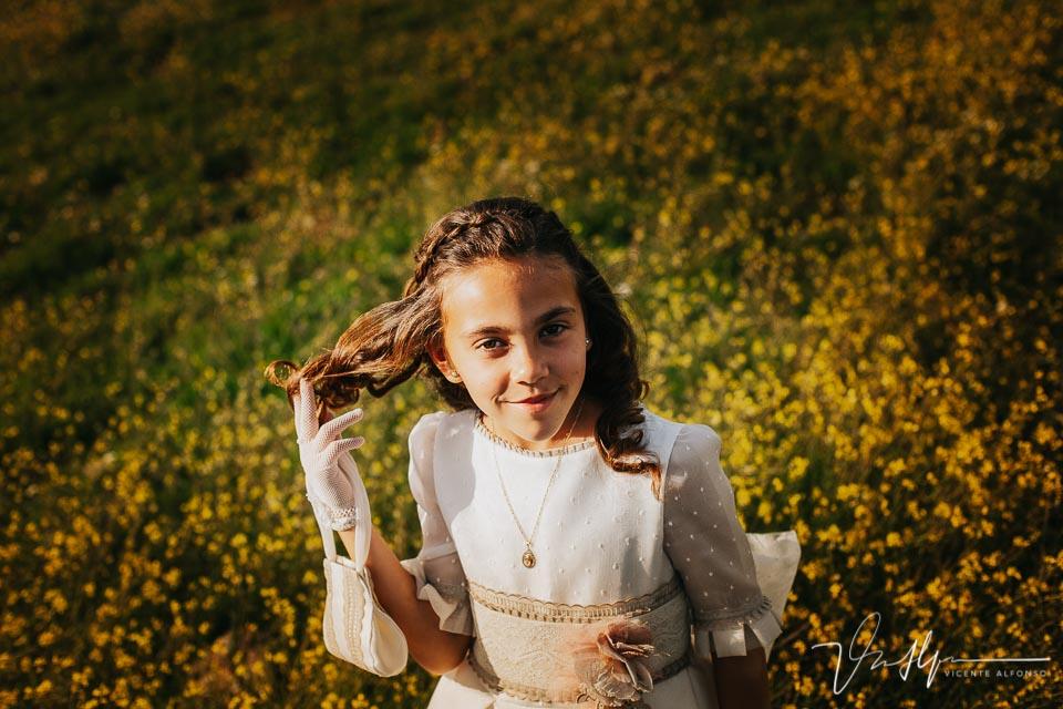 Retrato niña de comunión sujetándose el pelo