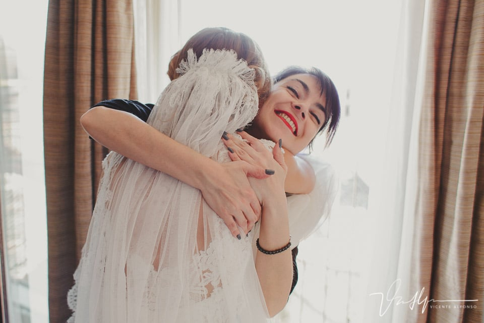 Novia abrazando a la amiga que la puso el velo