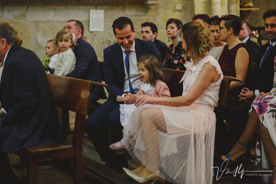 Niña en una boda dentro de la iglesia riendo