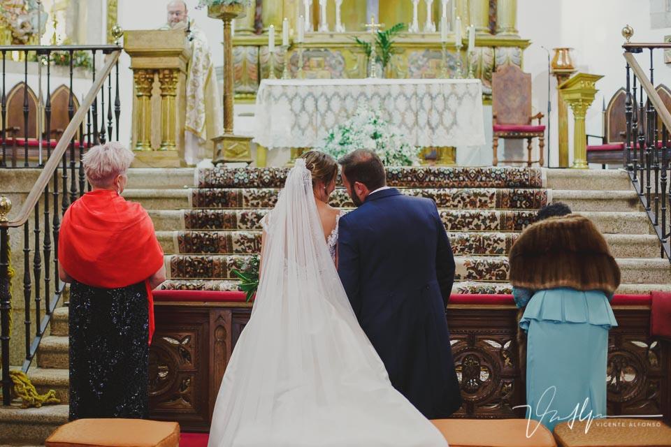 Novios juntando cabezas de espalda a la cámara dentro de la iglesia