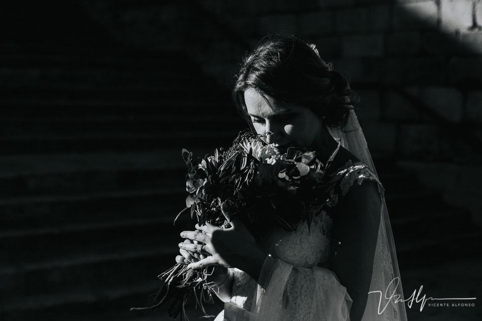 Novia mirando ramo en blanco y negro