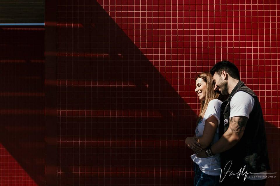 Pareja abrazada junto a una pared roja en la Playa de Badalona