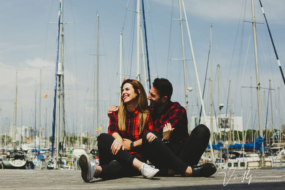 Pareja sentada en el suelo del puerto deportivo en Barcelona