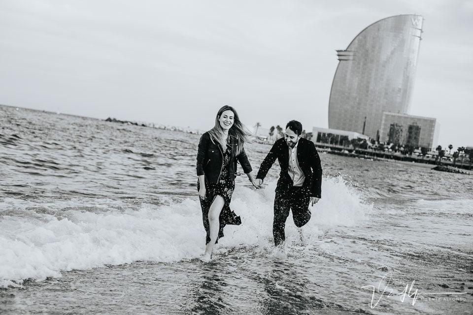 Pareja elegante corriendo por la playa de la Barceloneta junto al Hotel Vela W de fondo