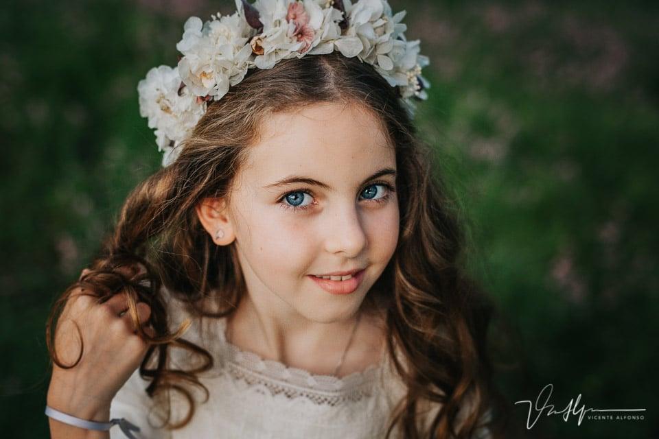 Preciosa niña de ojos azules sonriendo en su comunión