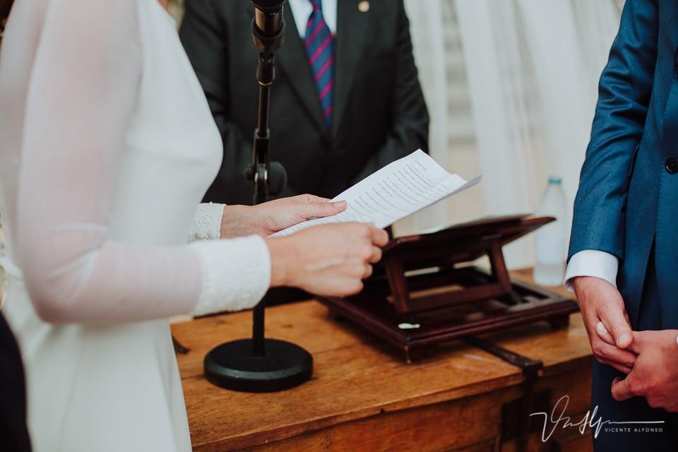 Detalle manos de la novia realizando la lectura
