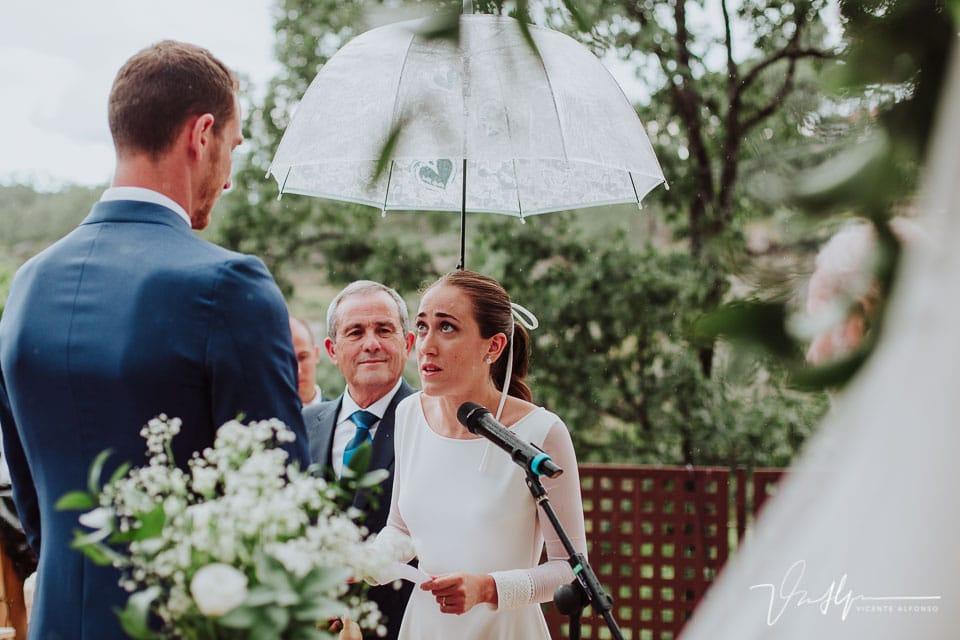 La novia leyendo amorosamente su lectura mientras su padre sujeta un paraguas