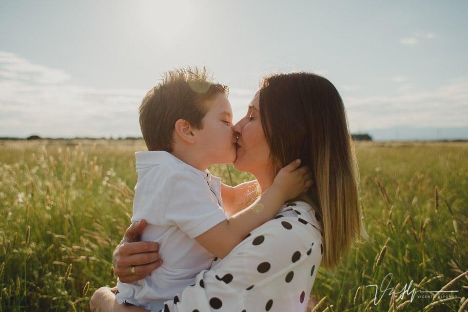 Hijo besando a su madre en la boca en el campo