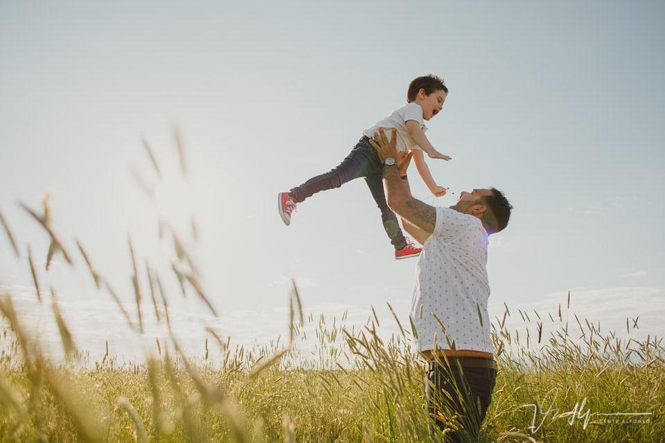 Padre lanzando a su hijo por los aires en el campo
