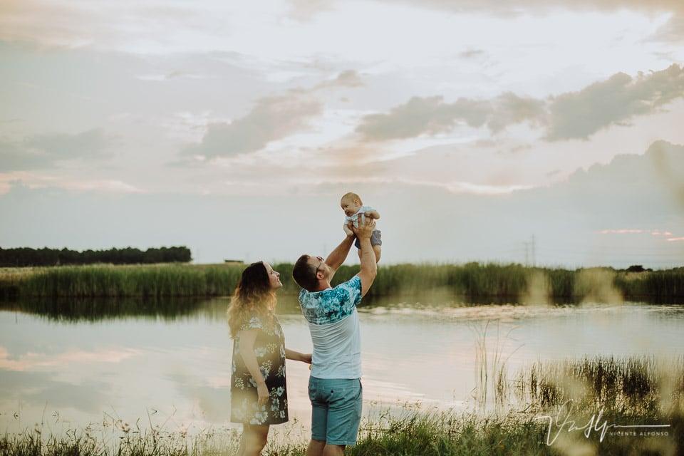 Padre levantando a su hijo junto a un estanque