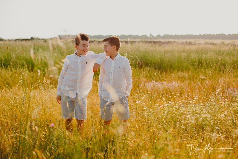 hermanos gemelos agarrados y riendo en el campo