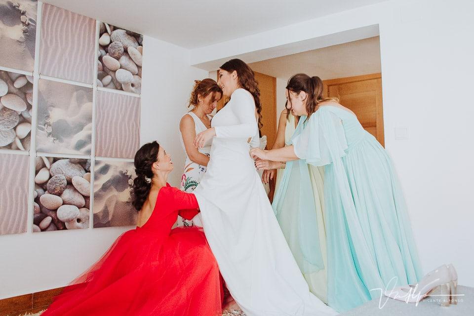 Amigas de la diseñadora poniéndola el traje de novia