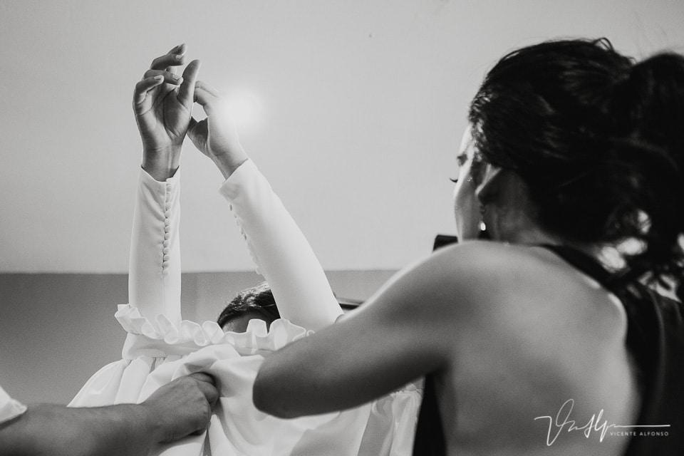 Colocándose la última parte del vestido de novia
