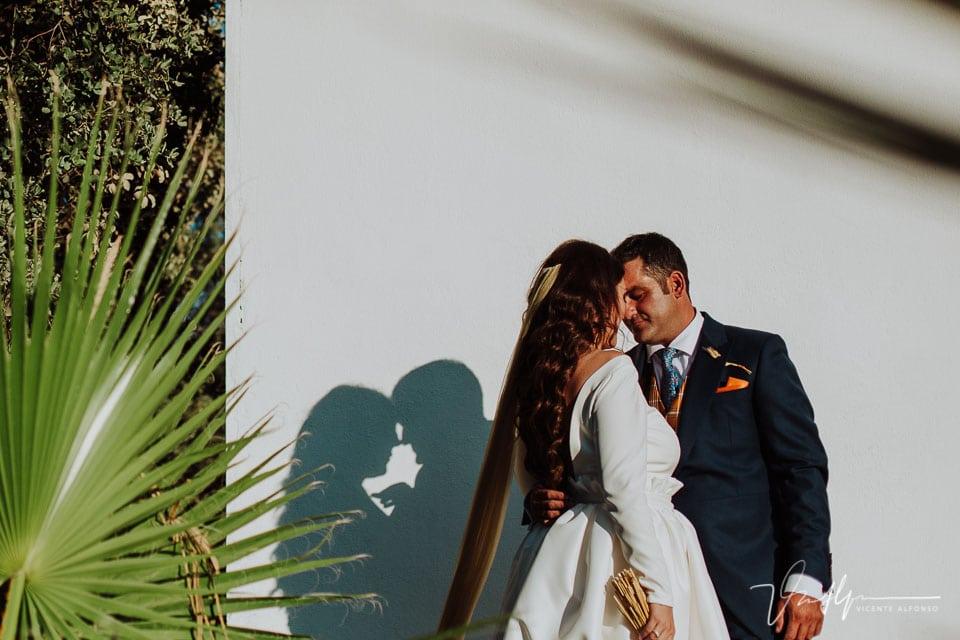 Novios sujetándose y detalle del vestido de boda de Alba García