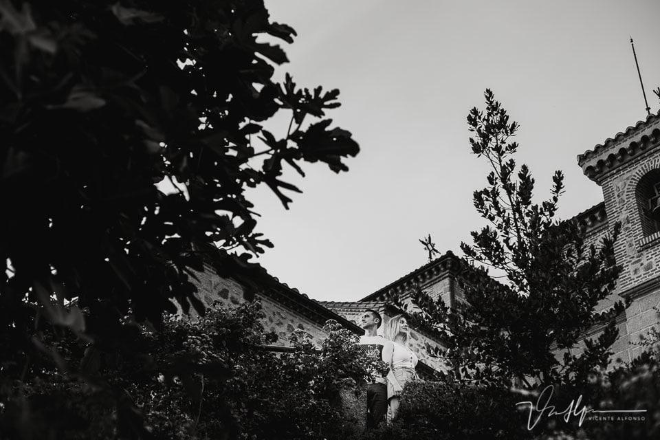 Pareja entre los árboles con la iglesia de Chilla al fondo en Candeleda
