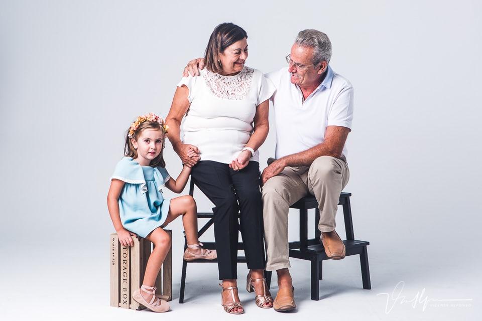 Niña con sus abuelos sentados en un estudio de fotografía
