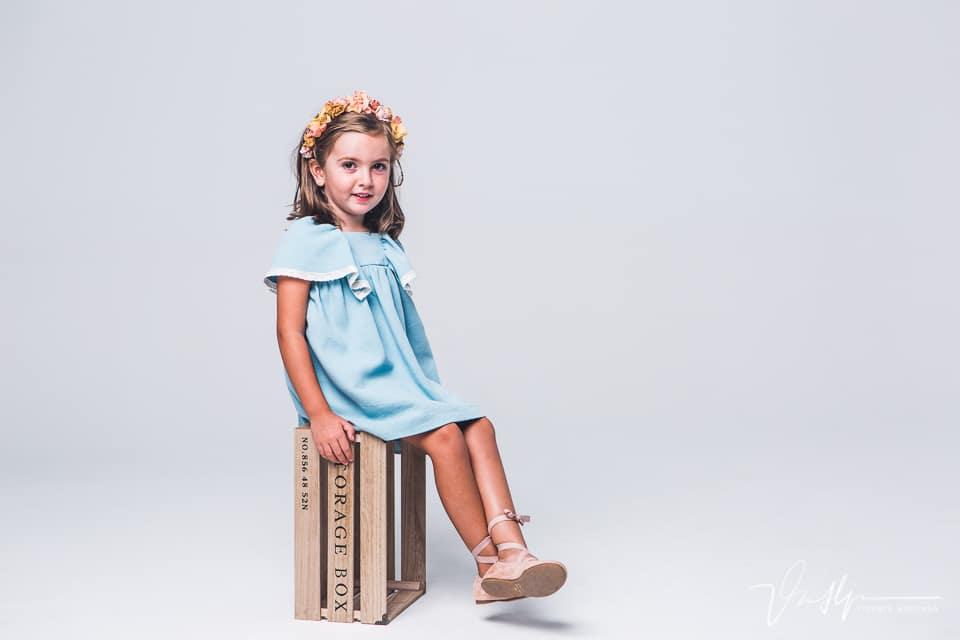 Niña sentada en una caja en fotografía de estudio