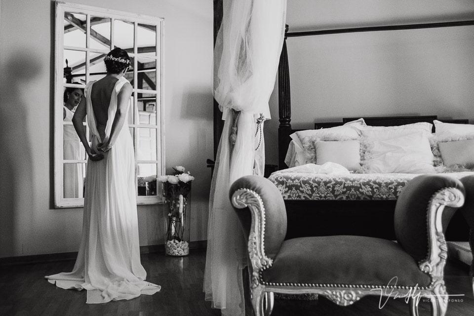 La novia en el ruta imperial gasto eventos abrochándose el vestido