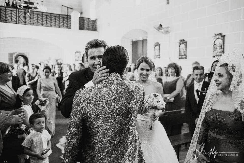 Abrazo en la iglesia entre padrino y novio