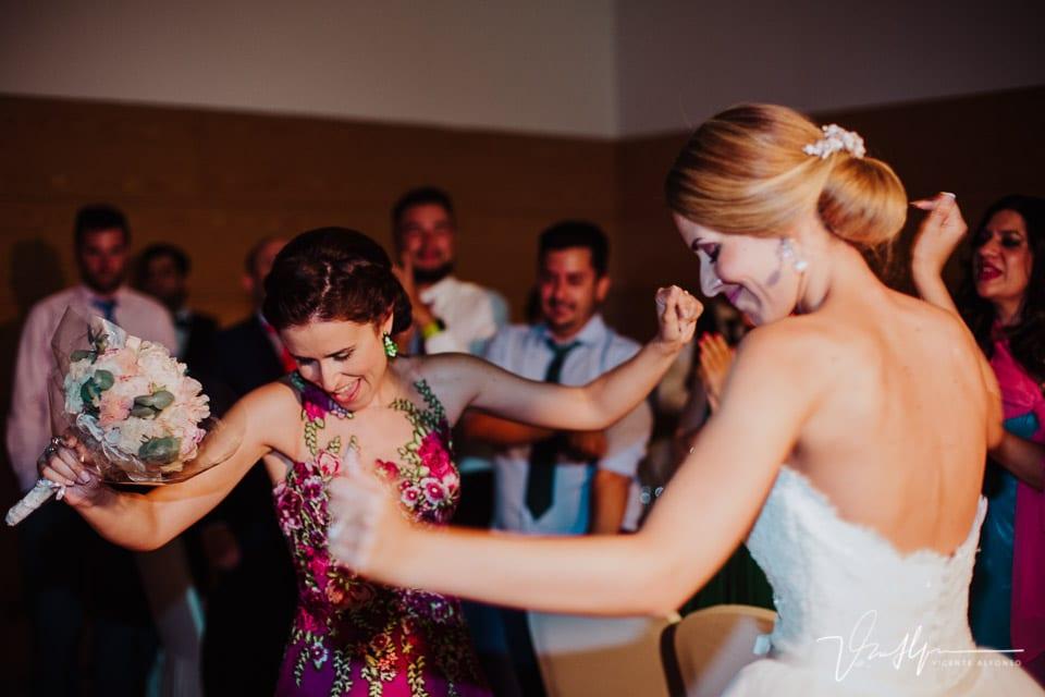 Novia bailando con su hermana al entregar el ramo