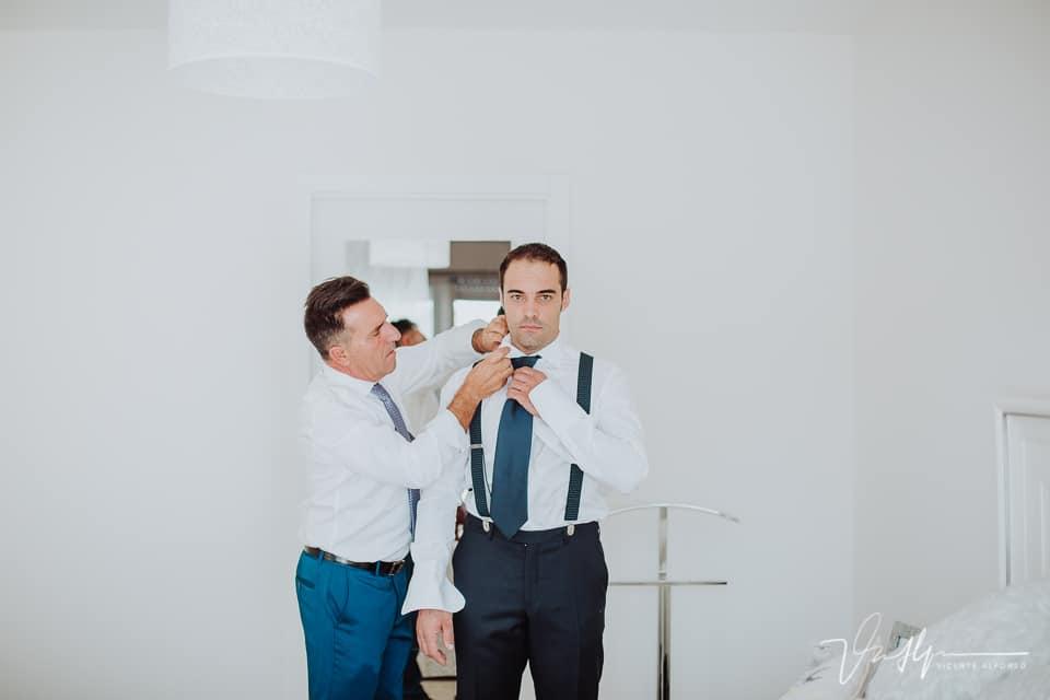 El novio ayudado por su tío mientras se pone la corbata