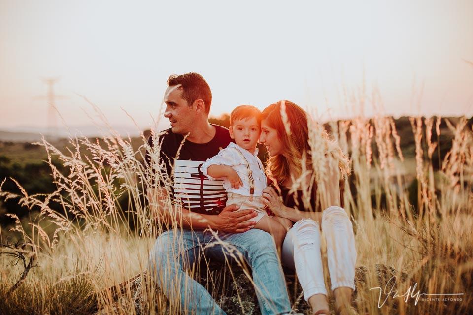Familia abrazando a su hijo entre espigas al atardecer