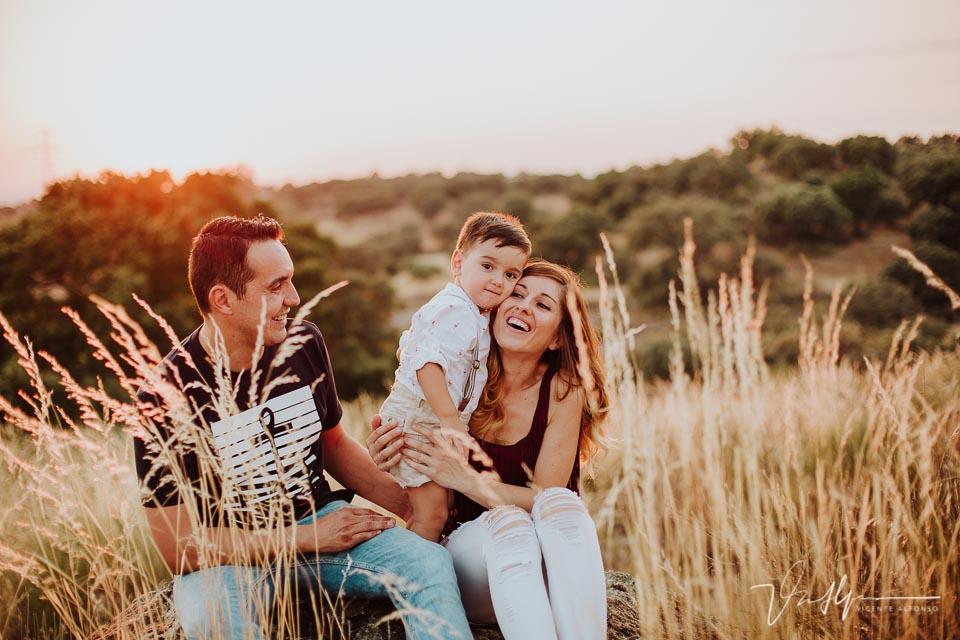 Familia abrazando a su hijo entre espigas sonriendo al atardecer