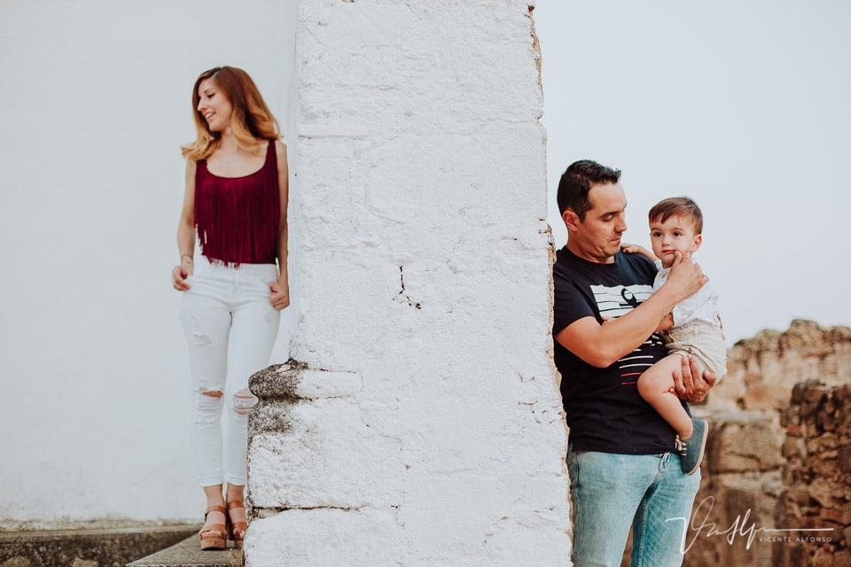 Padre abrazando a su hijo con su mujer al otro lado de la pared