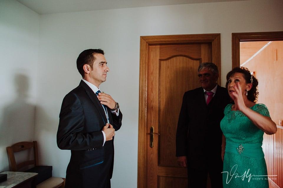 Novio colocándose la corbata antes de salir a la ceremonia