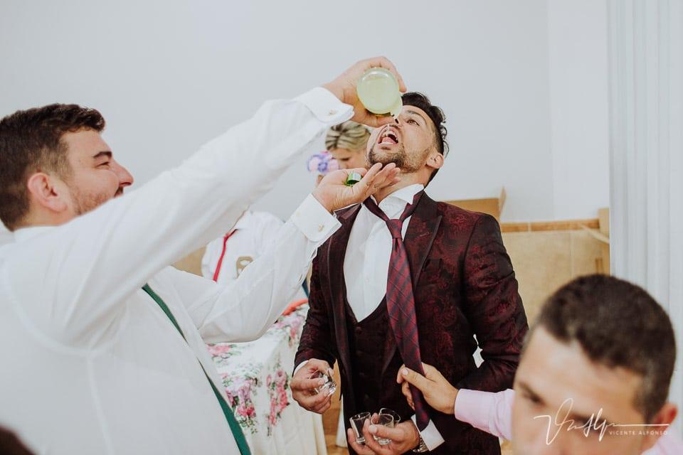 Amigos del novio ofreciendo licor al novio