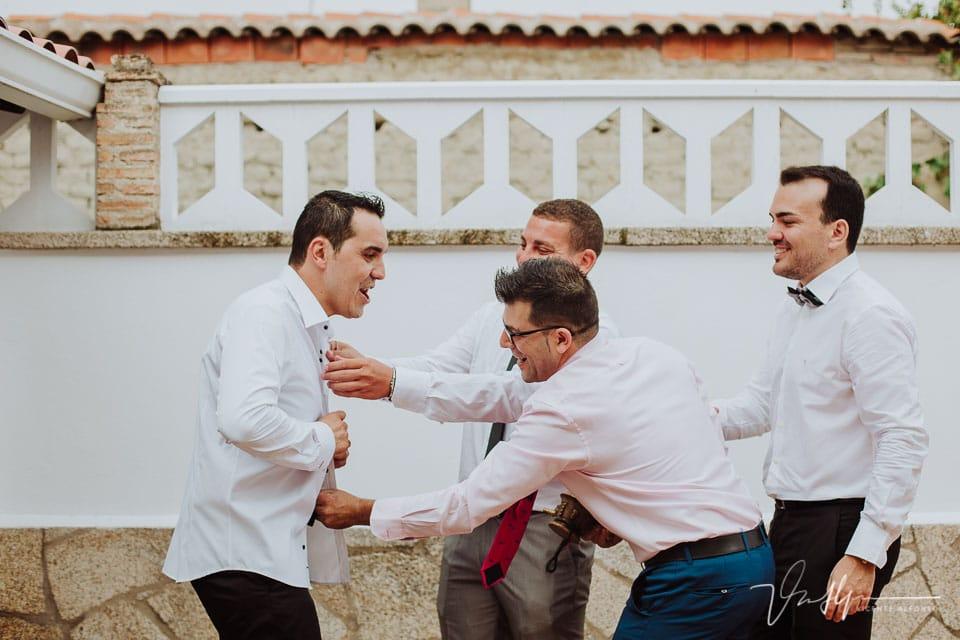 amigos del novio riendo mientras le ponen la camisa