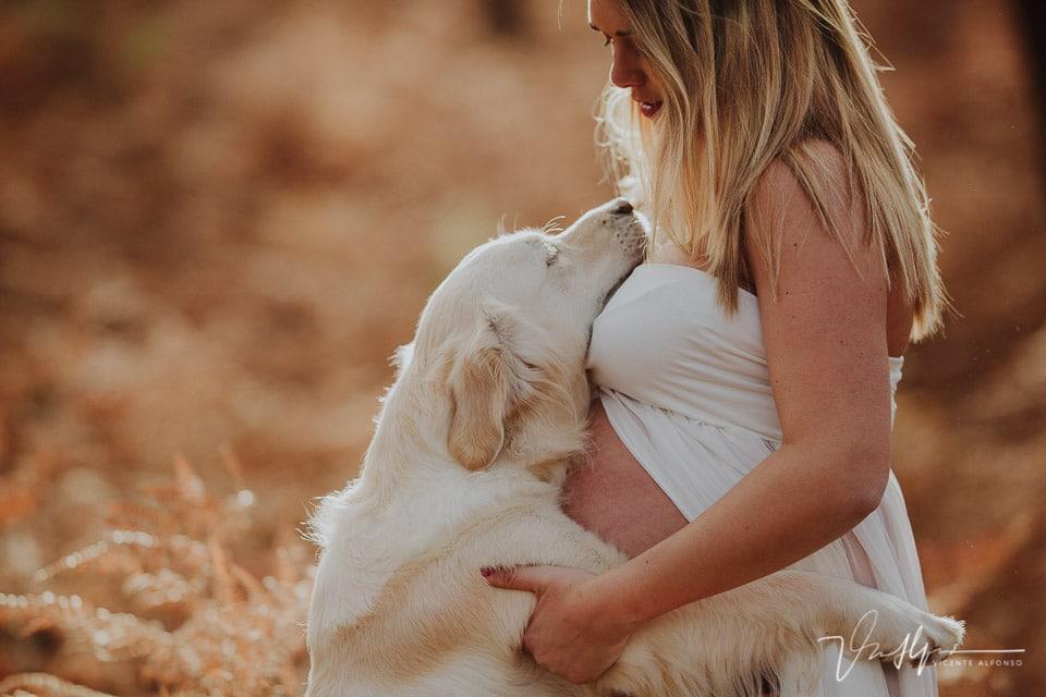 Embarazada abrazando a su perro en la Sierra